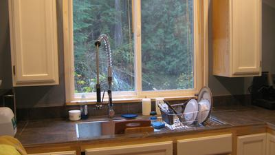Kitchen looks out onto the river, forrest, and waterfall